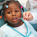 Photo of a little girl having her teeth exam by a dentist.