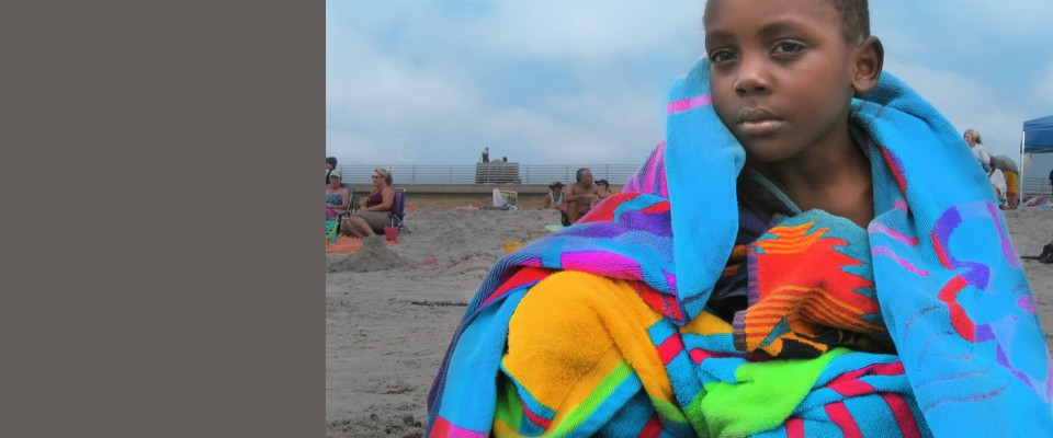 Young African Refugee Boy Sitting on San Diego Beach Sand, Wrapped in a Very Colorful Beach Towel