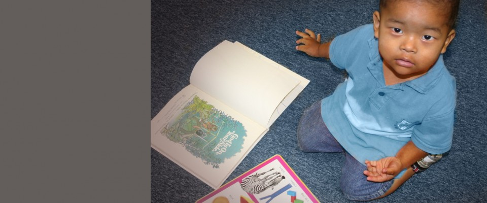 Preschool-Age Refugee Boy Sitting on the Floor, Surrounded by Alphabet Books