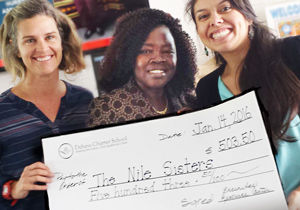 Photo of Elizabeth Lou and Kimberly accepting a donation from Dehesa Charter School