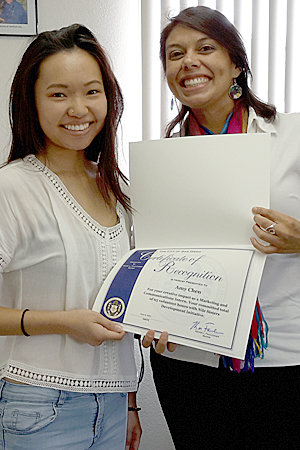 Photo of Kimberly Castillo and college intern Amy Chen receiving a certificate of recognition from San Diego Mayor Kevin Falconer
