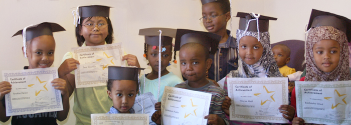Eight Elementary School-Aged Refugee Children Smiling and Holding Up Achievement Award Certificates