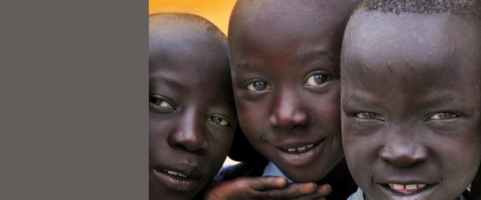 Photo of three young smiling South Sudanese boys.