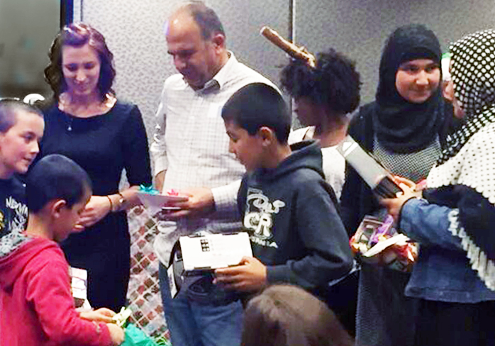 National University Holiday Cheer matches refugee families with adoptive sponsors at a gifting event
