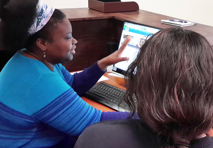 Photo of Marie Saint Louis, Community Health Advocate, helping a French-speaking client to complete a Covered California online application