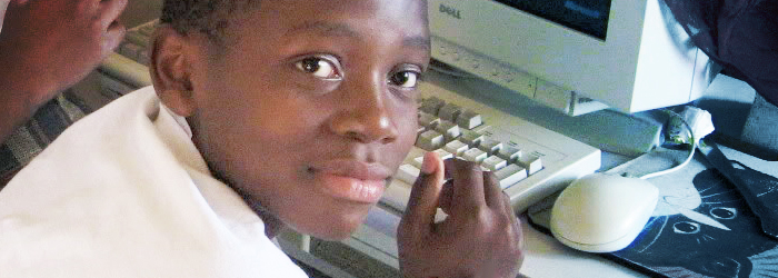 Teen-Aged African Refugee Boy Using a Computer